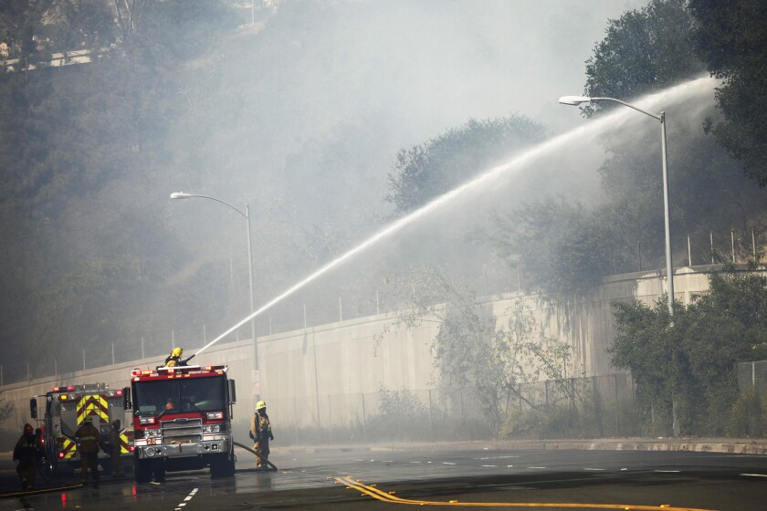 Firefighters on Harvey Drive hose down brush along the 2 Freeway.