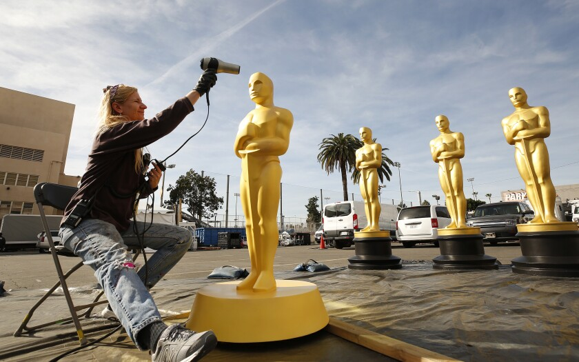 Lead scenic artist Dena D'Angelo dries freshly painted Oscar statues in preparation for Sunday's 92nd Academy Awards ceremony at the Dolby Theatre in Hollywood.