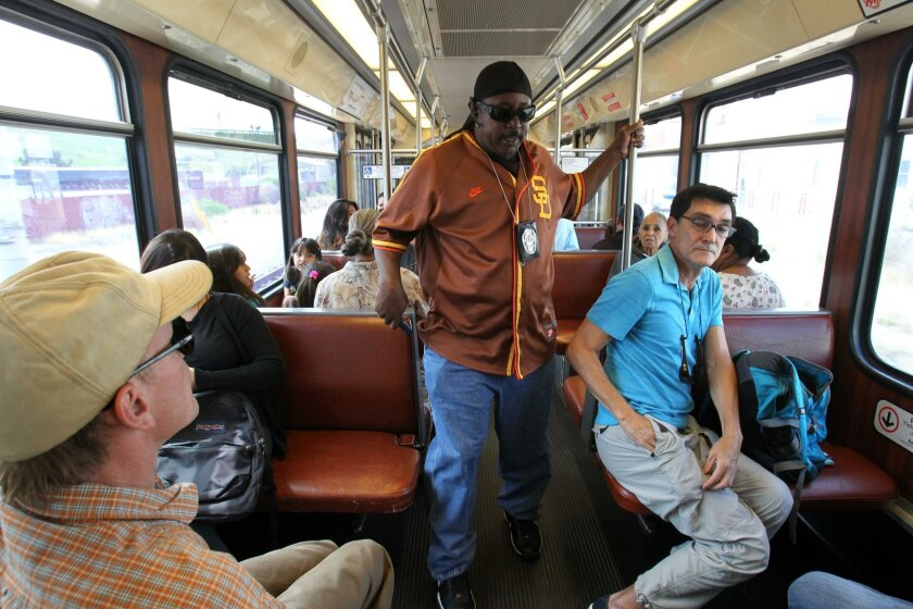 Transit System Security Officer Marlon Wells walked down the aisle of a southbound Trolley after announcing he and his partners were security and hanging their badges around their necks.