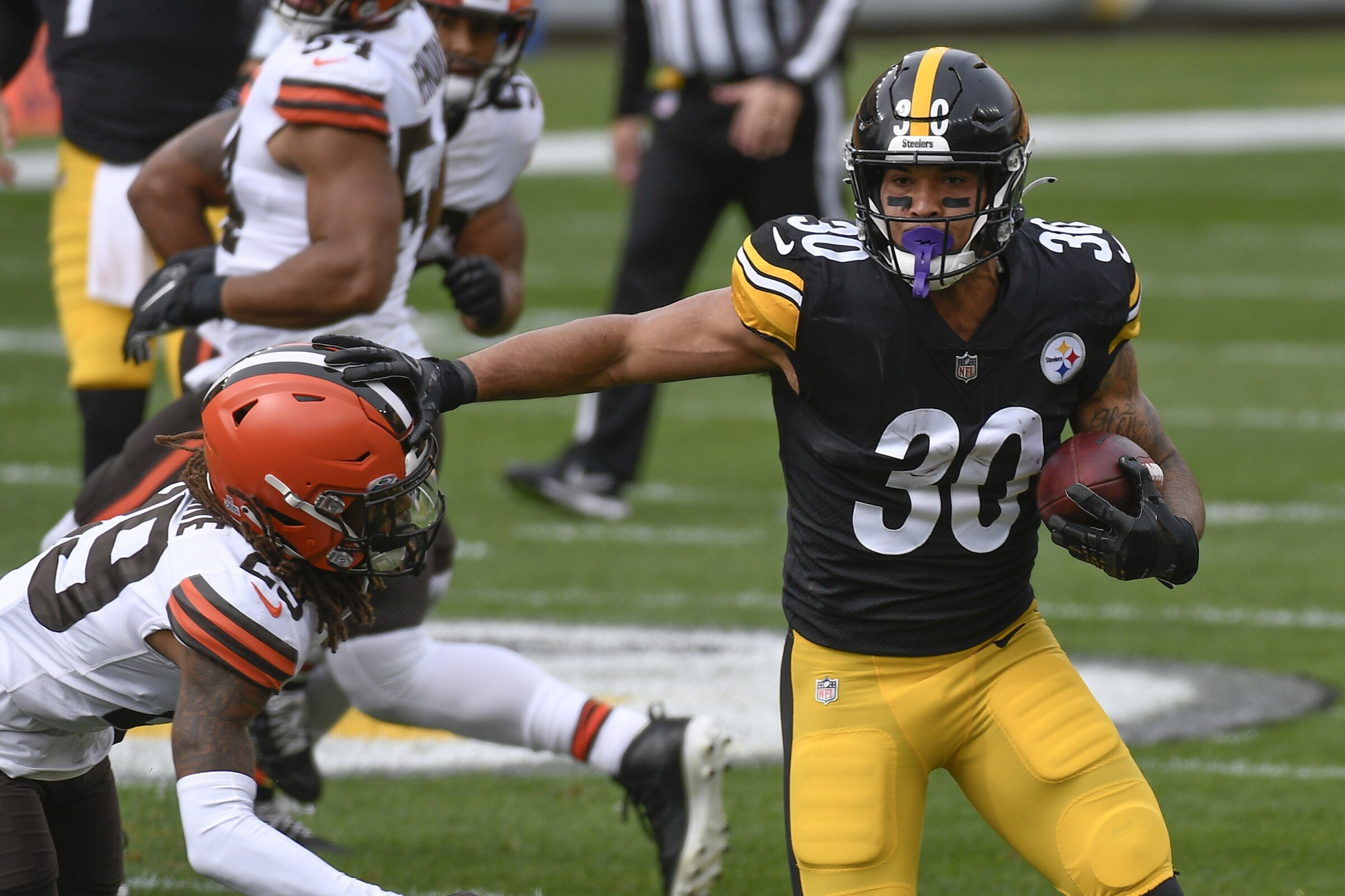 Pittsburgh Steelers running back James Conner runs past Cleveland Browns safety Sheldrick Redwine.