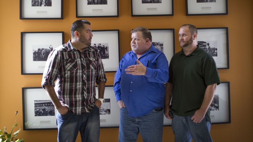 Plaintiffs Peter Guzman, left, Dan McKibben, and Sean Lint are shown in 2014 at ACLU headquarters in Los Angeles, after their class-action lawsuit was announced alleging discrimination against gay, bisexual and transgender inmates at the West Valley Detention Center.