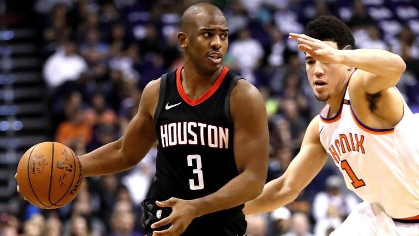 Houston Rockets guard Chris Paul (3) drives against Phoenix Suns guard Devin Booker (1) during the f