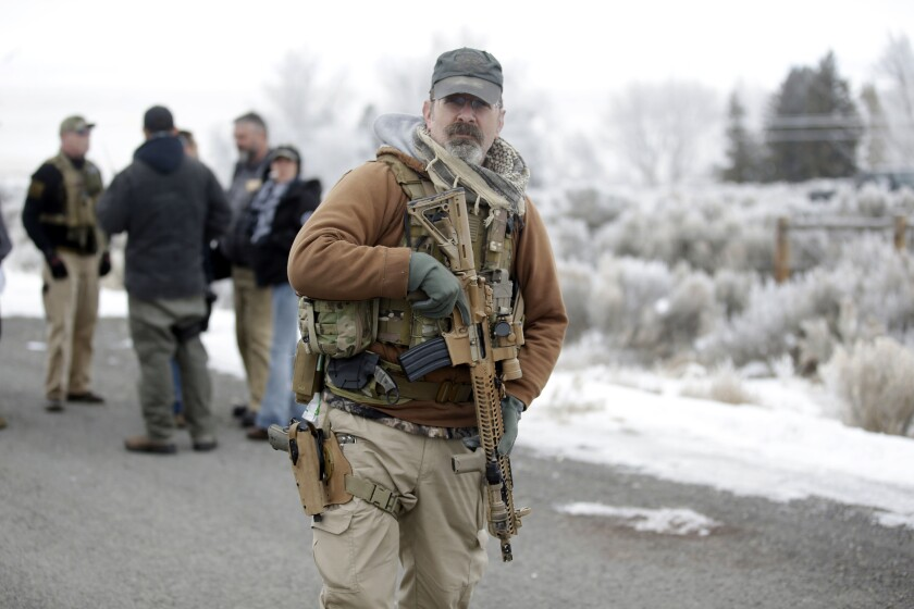 A man stands guard at the Malheur National Wildlife Refuge near Burns, Ore., in this Jan. 9, 2016 file photo.