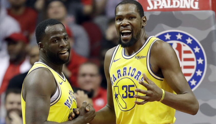 Golden State Warriors forwards Kevin Durant (35) and Draymond Green appear to put their differences aside during a game in Houston on Nov. 15.