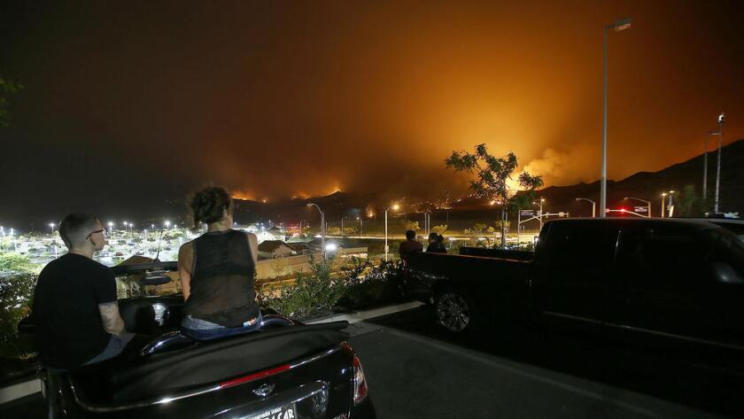 Los espectadores se reúnen en un centro comercial a lo largo de Golden Valley Road, en Santa Clarita, para ver el incendio en las colinas de la ciudad el domingo por la noche.