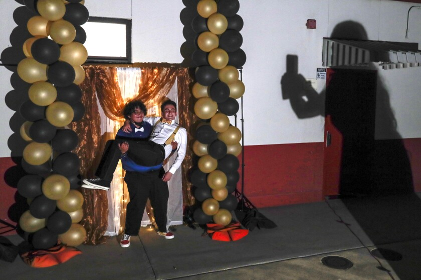 Baldwin Park, CA, Tuesday, May 18, 2021 - Jesus Medina hoists Jose Gonzalez for a photo taken by Jade Magallanes (shadow) at the Sierra Vista High School on-campus prom. (Robert Gauthier/Los Angeles Times)