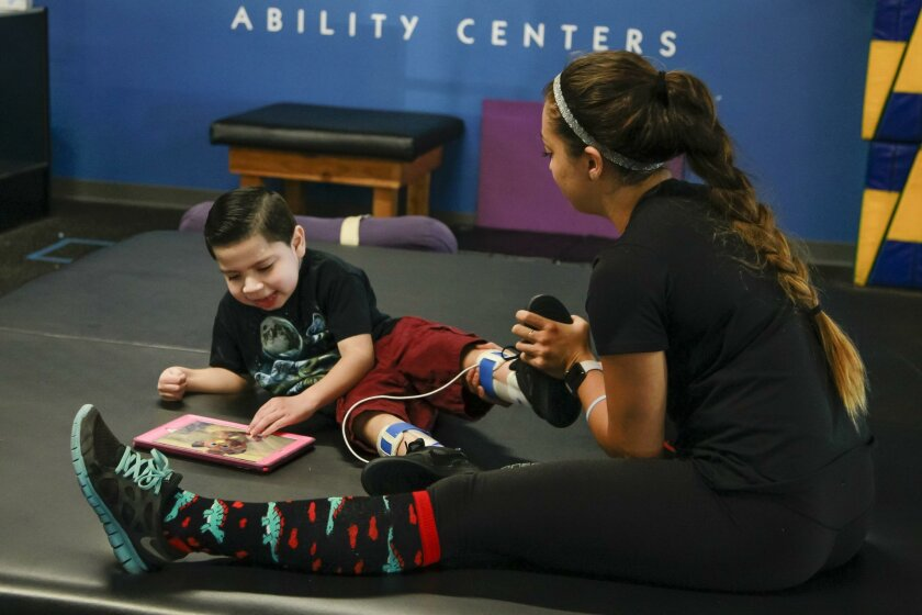 Izaiah Wallis, 6, stretches during his therapy visit with recovery specialist Amanda Diesen on Friday at Project Walk in Carlsbad.