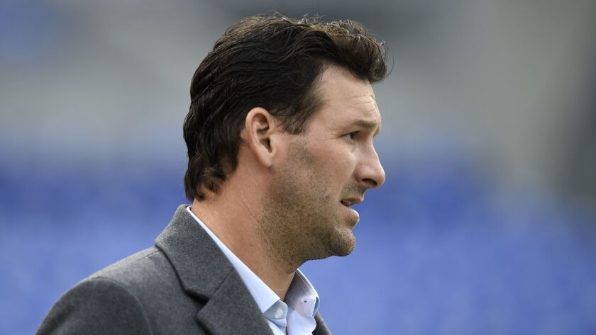 Former Dallas Cowboys quarterback Tony Romo walks on the field before an NFL football game between t