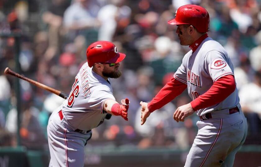 Tucker Barnhart (i) de los Rojos de Cincinnati extiende la mano a su compañero de equipo Joey Votto (d). EFE/Archivo