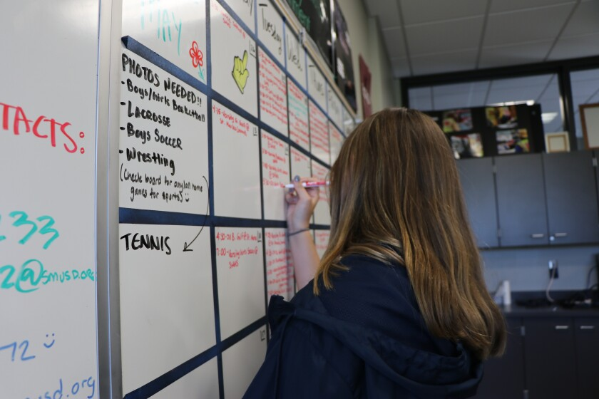 Gianna Mosca, a 10th-grader at San Marcos High, writes notes on the planning board for this year's student yearbook