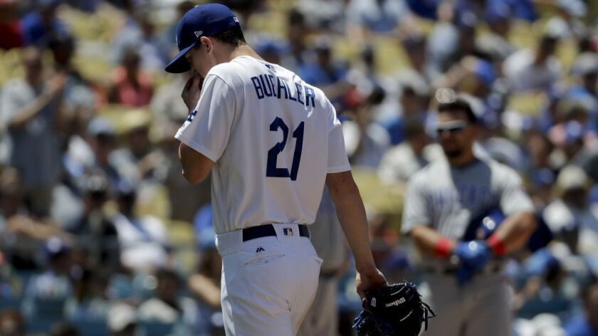 Los Angeles Dodgers starting pitcher Walker Buehler wipes his face after being taken out of the game