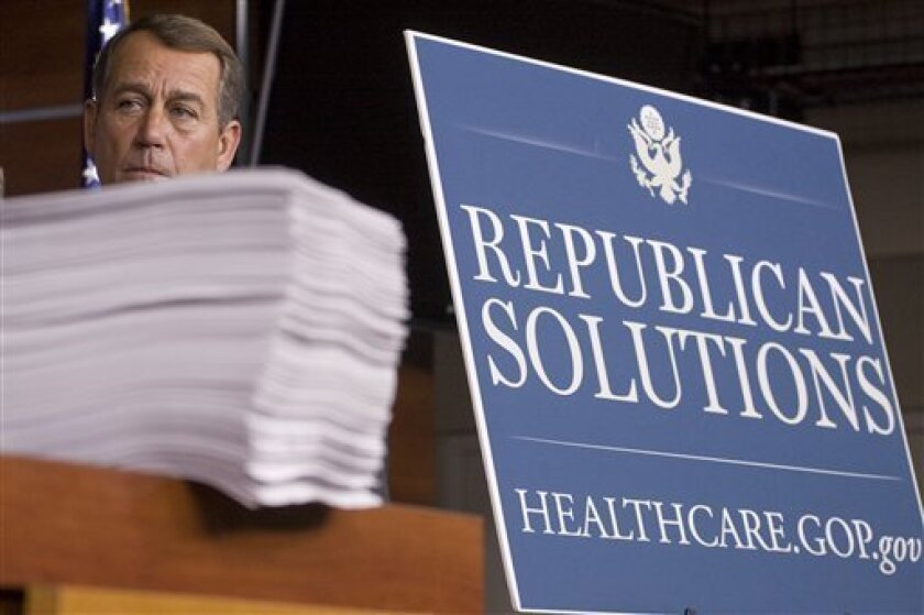House Minority Leader John Boehner of Ohio stands behind a copy of the Democrat's version of the health care bill during a news conference on Capitol Hill in Washington, Thursday, Oct. 29, 2009. (AP Photo/Harry Hamburg)