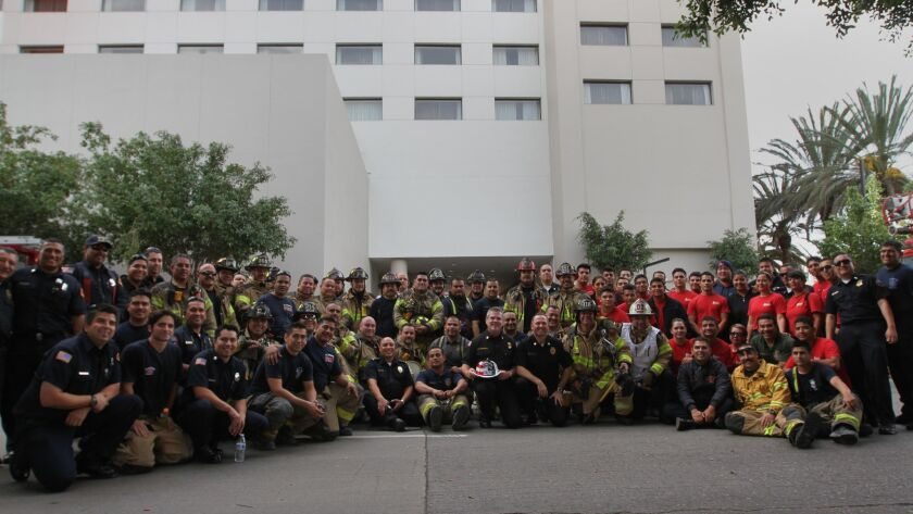 Following a joint training exercise on high-rise fire rescues, fire fighters from San Diego and Tijuana pose outside the Hotel Real Inn in Tijuana.