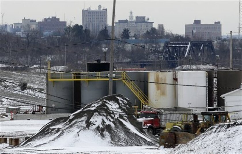 FILE - In this Wednesday, Jan. 4, 2011 file photo, a brine injection well owned by Northstar Disposal  Services LLC is seen in Youngstown, Ohio, with the skyline of Youngstown in the distance. A dozen earthquakes in northeastern Ohio were almost certainly induced by injection of gas-drilling wastew