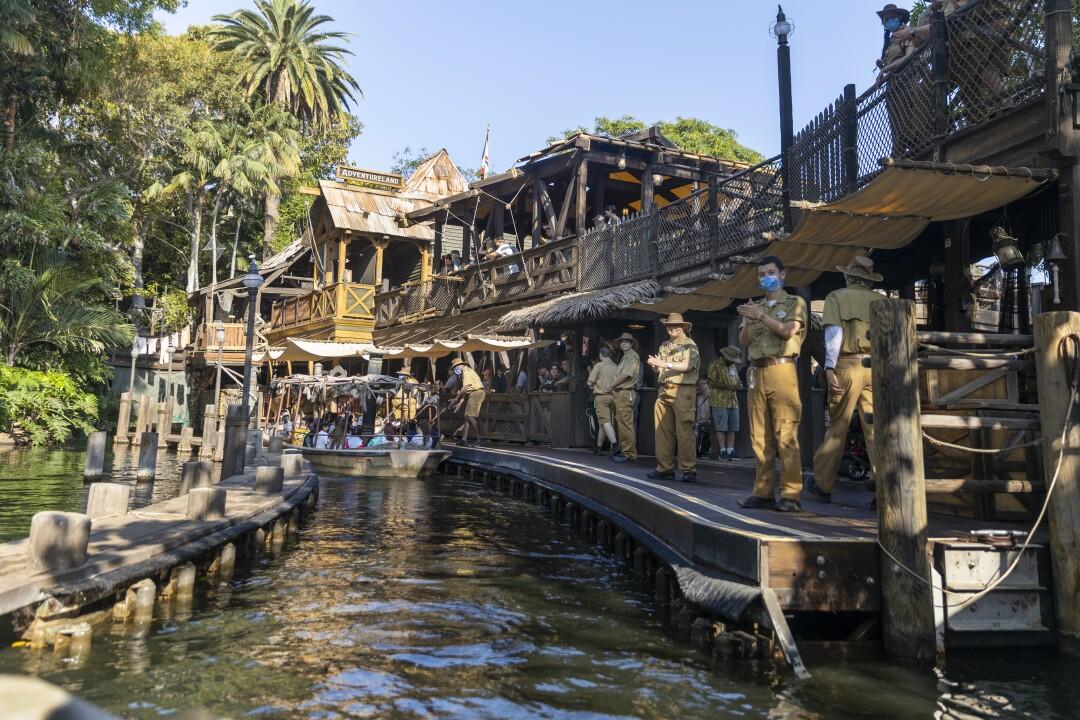 Passengers disembark the Jungle Cruise ride while staff in khakis applaud