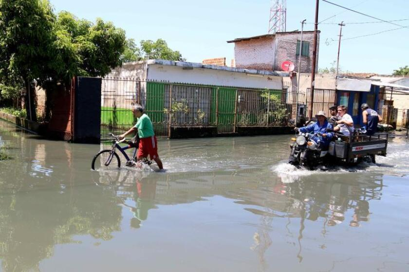 -People move along a flooded street on Dec. 4, 2018, on Asuncion's river banks, where many inhabitants have been forced to live in the unhealthiest of conditions caused by the stagnant water submerging its streets from the flooding Paraguay River, and which has driven 7,500 families out of their homes. EFE-EPA/Andres Cristaldo