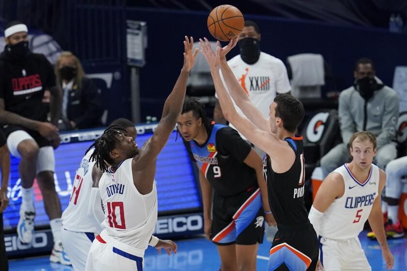 Oklahoma City Thunder forward Aleksej Pokusevski (17) shoots over Los Angeles Clippers center Daniel Oturu (10) in the second half of an NBA basketball game Sunday, May 16, 2021, in Oklahoma City. (AP Photo/Sue Ogrocki)