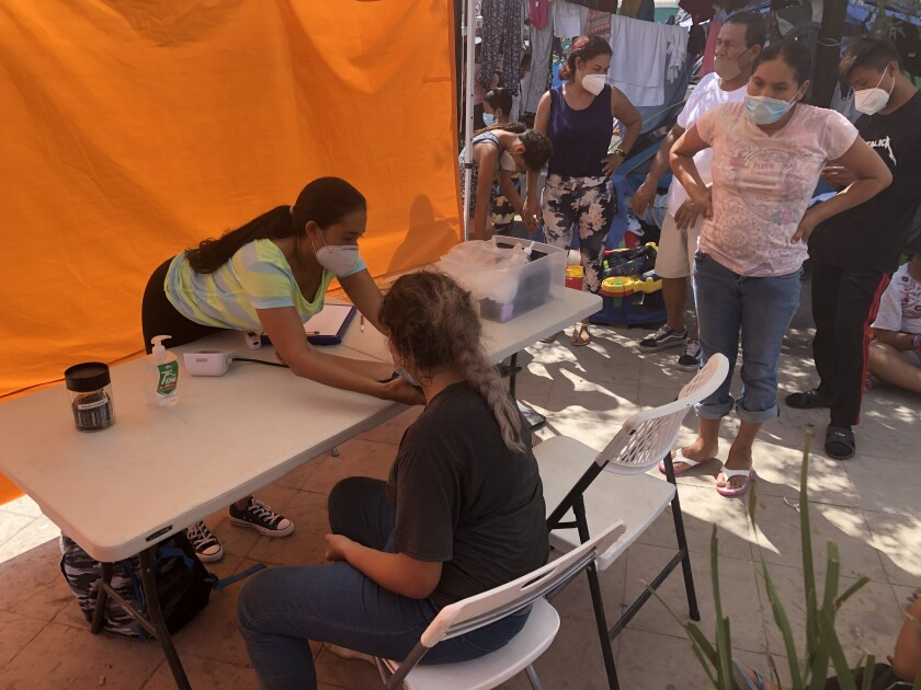 A woman reaches toward a woman seated across a table at the migrant camp in Reynosa, Mexico, as others wait.