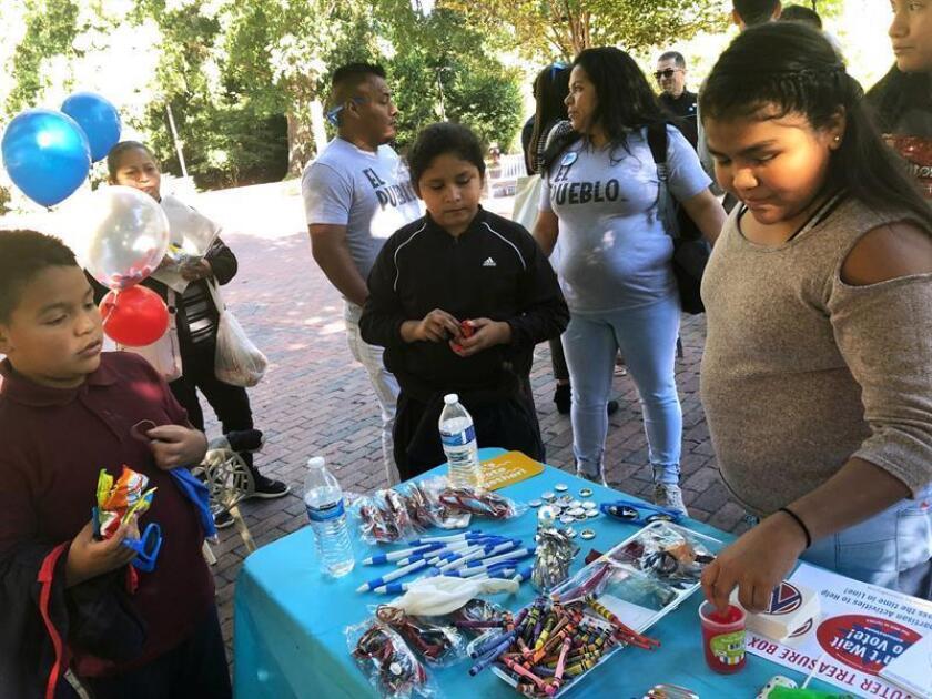 """Fotografía cedida por la organización """"MomsRising"""" en donde aparecen unos niños recogiendo caramelos y recuerdos durante la campaña de """"MomsVote"""", """"No puedo esperar para votar"""", celebrada el pasado 27 de octubre de 2018, en la ciudad de Winston Salem, Carolina del Norte. EFE/MomsRising/SOLO USO EDITORIAL/NO VENTAS"""