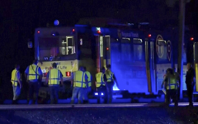 In this image from video, emergency workers gather around a light rail train Thursday in Sacramento that crashed into another train, injuring more than two dozen people.