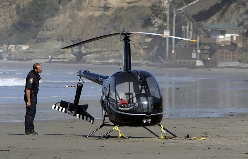 Sheriff's deputies and state parks officials monitor the scene where a Robinson R22 helicopter made an emergency landing on the beach south of Swami's shortly after 8 a.m.