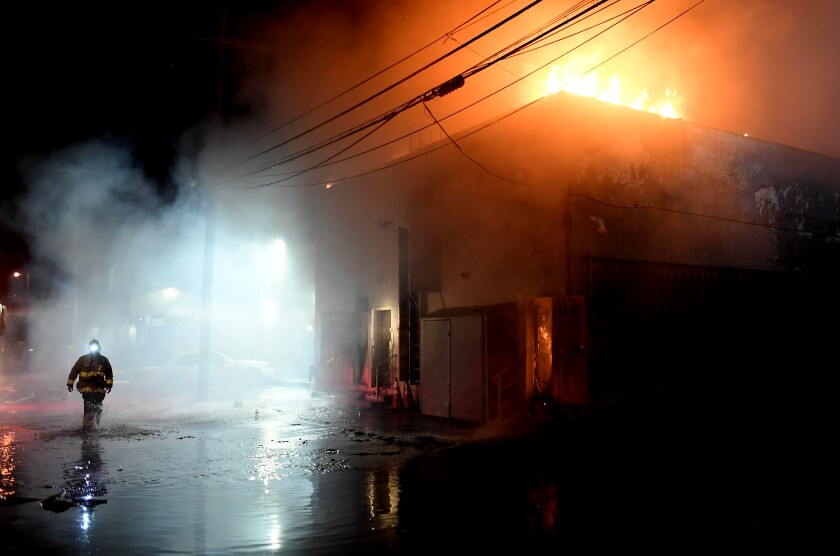 A firefighter walks behind a burning building on Melrose Avenue during civil unrest in Los Angeles on Saturday.