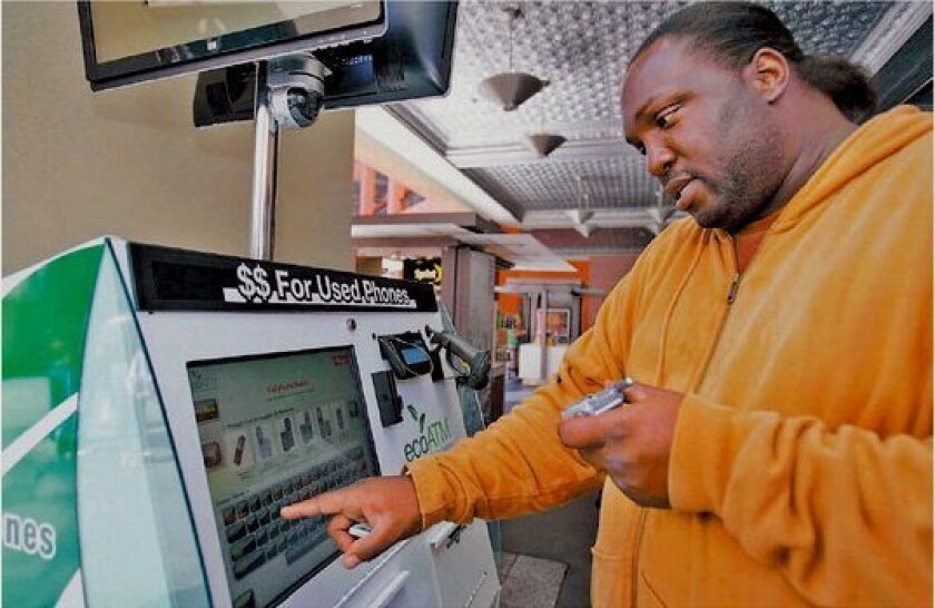 A customer types in his old phone's model number to find out its worth at an ecoATM recycling kiosk in downtown San Diego in  2016.