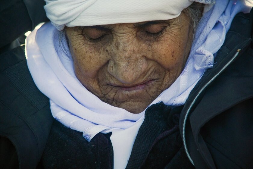An elderly woman from Afghanistan reacts after her arrival on a dinghy with other migrants and refugees in the village of Skala Sykaminias, on the northeastern Greek island of Lesbos, Wednesday, Jan. 27, 2016. Greek authorities say a total of seven bodies, including those of two children, have been recovered from the sea off the eastern Aegean island of Kos after a boat carrying migrants or refugees sank early Wednesday. (AP Photo/Mstyslav Chernov)