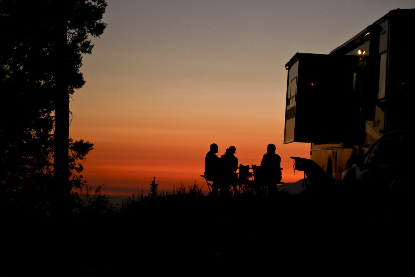 A beautiful orange sunset view with silhouette of campers in the foreground.