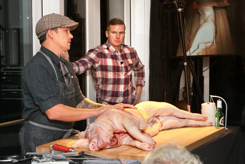 James Holtslag, left, and Trey Nichols of The Heart & Trotter Butchery in North Park get set to break down a pig at the sold-out kickoff dinner at last year's San Diego Wine & Food Festival at Tidal. While anathema to many animal rights activists, nose-to-tail event organizers emphasize using the w