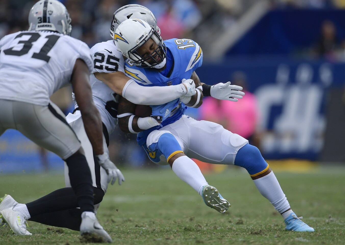 Los Angeles Chargers wide receiver Keenan Allen, center, is hit by Oakland Raiders defensive back Erik Harris during the second half of an NFL football game Sunday, Oct. 7, 2018, in Carson, Calif.
