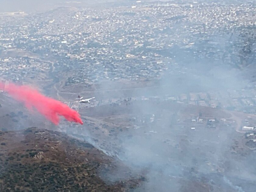 A plane drops fire retardant on flames burning in open terrain just north of the border and east of Otay Mesa on Monday afternoon.