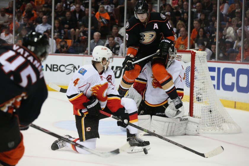 Ducks forward Corey Perry tries to shield Flames goalie Karri Ramo as he deflects a shot from teammate Sami Vatenen during the first period of a Western Conference semifinal game Sunday at Honda Center.