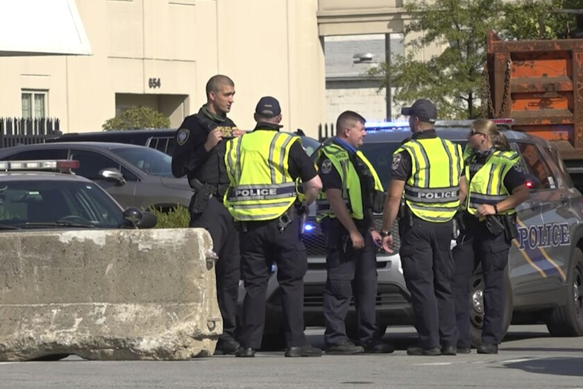 Police officers stand near barriers added to block access to downtown Louisville, Ky.