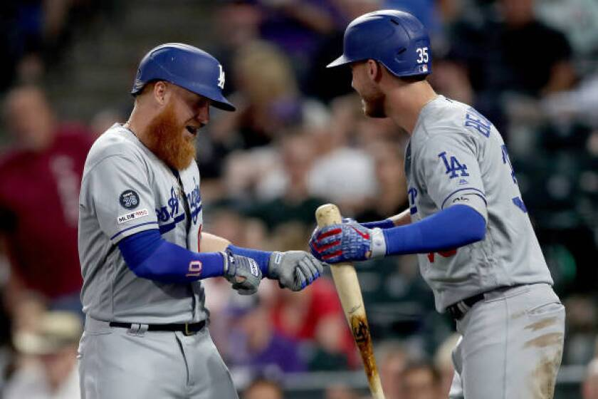 Dodgers' Justin Turner, left, celebrates with Cody Bellinger after hitting a two-run home run in the fourth inning against the Colorado Rockies.