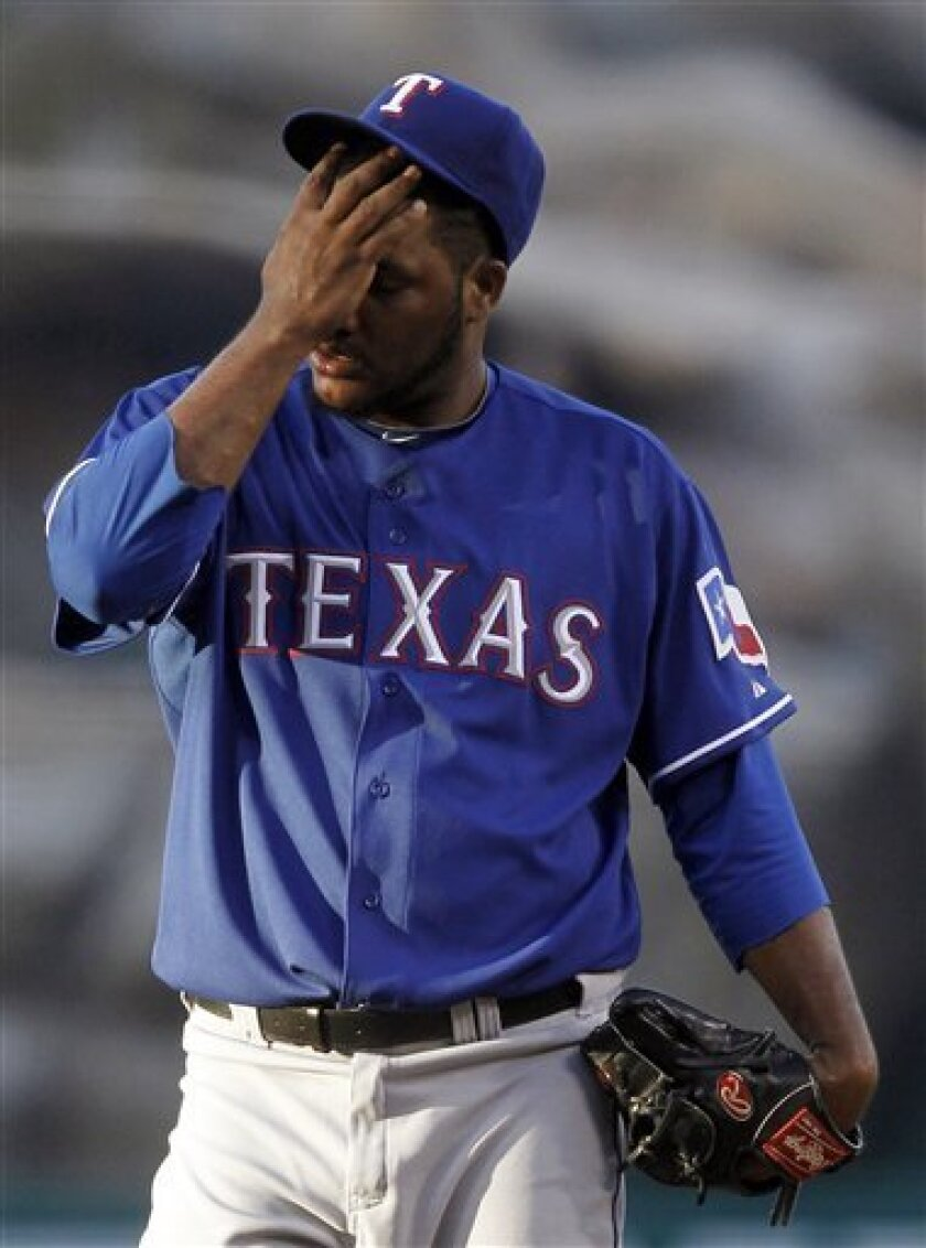 Texas Rangers starting pitcher Omar Beltre wipes his face after giving up a solo home run to Los Angeles Angels' Erick Aybar during the first inning of a baseball game in Anaheim, Calif., Wednesday, June 30, 2010. (AP Photo/Chris Carlson)