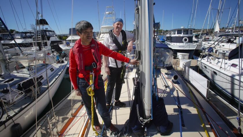 Mitsuhiro Hiro Iwamoto (left) and Doug Smith (right) stand on the deck of their 40-foot sailboat, Dr