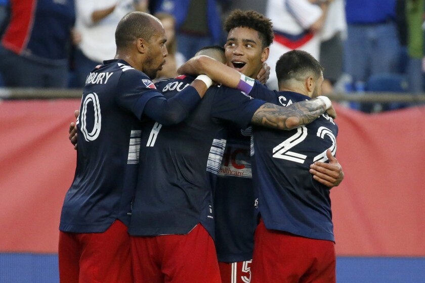 New England Revolution midfielder Brandon Bye (15) hugs teammate Gustavo Bou after he assisted on a goal by Bou as teammate Teal Bunbury (10) and Carles Gil (22) join in during the second half of an MLS soccer match against CF Montreal, Sunday, July 25, 2021, in Foxborough, Mass. (AP Photo/Mary Schwalm)