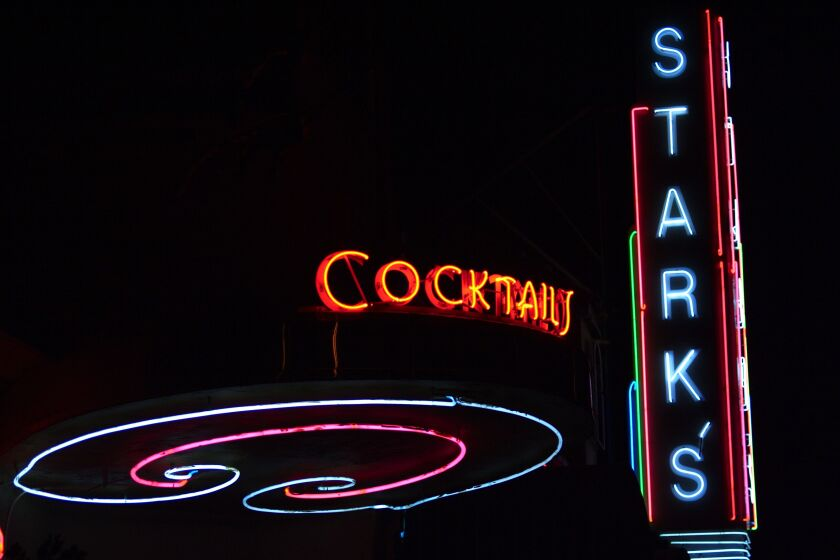 """Neon signs say """"cocktails"""" and """"Stark's."""""""