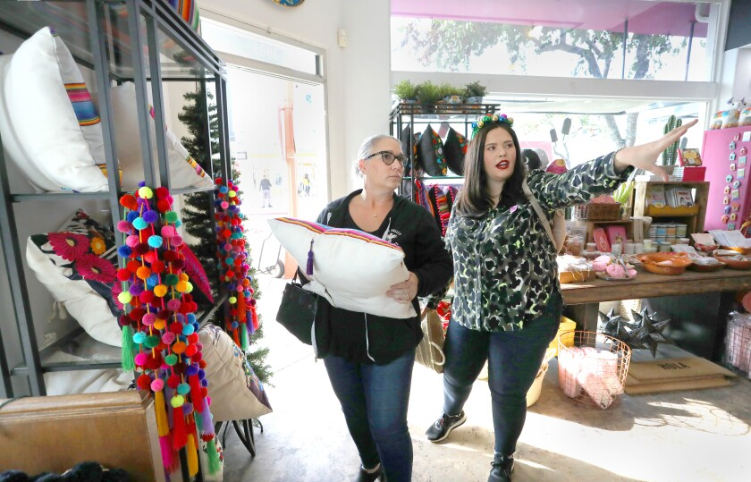 Margaux Dinerman, left, listens to Mariel Romero who works at Artelexia, a North Park store specializing in decorative items from Mexico.