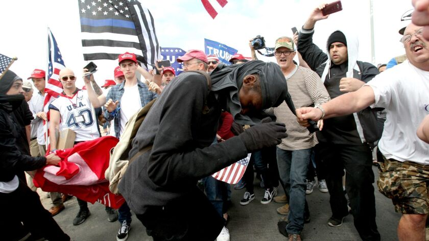 A protestor gets pulled by the Make America Great Again March crowd at Bolsa Chica State Beach in Hu