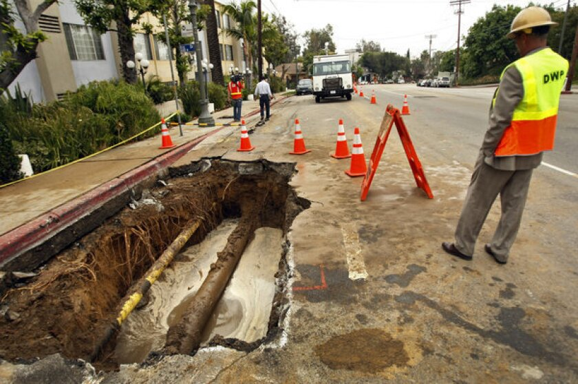 A Los Angeles Department of Water and Power supervisor at the scene of a water main break in Hollywood in May. The 12-inch cast iron pipe was installed in 1931.