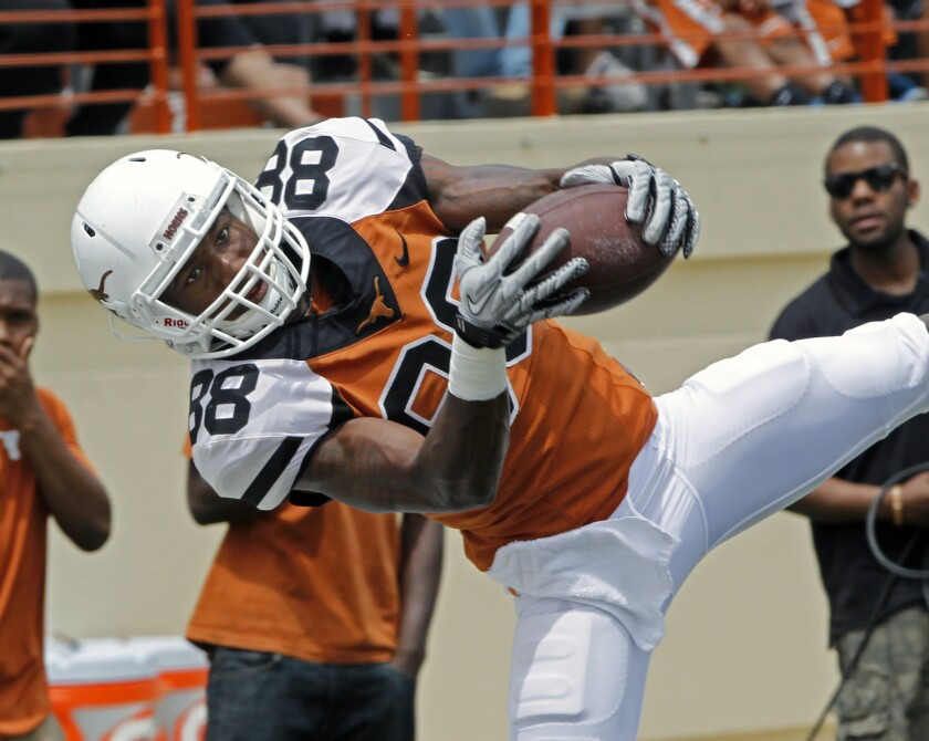 University of Texas football player Montrel Meander comes down with a pass during the first half of the Orange and White football game in Austin, Texas, on April 19. Meander and another Texas football player, Kendall Sanders, were charged with sexual assault Thursday.