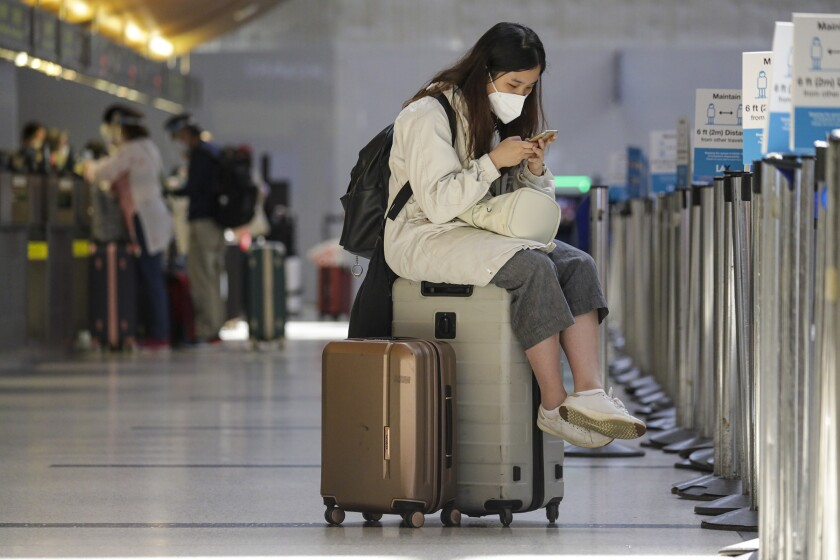 A woman in a mask sits on her luggage while looking at her phone