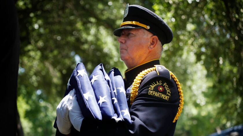 A Dallas police officer carries flags during burial services for Senior Cpl. Lorne Ahrens in July 2016. Ahrens was one of five law enforcement officers killed in an ambush.