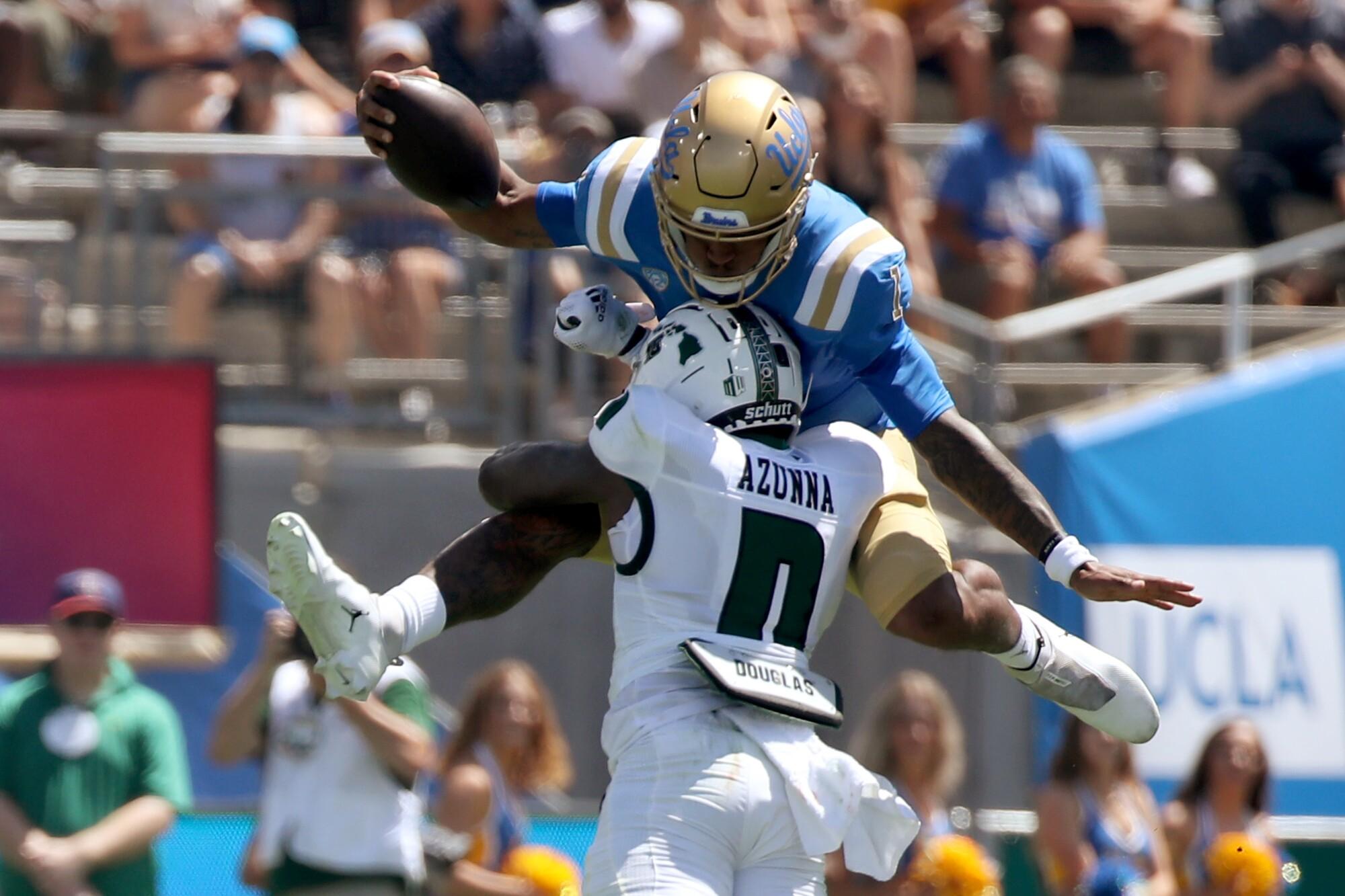 UCLA quarterback Dorian Thompson-Robinson tries to hurdle  Hawaii defender Chima Azonnah.