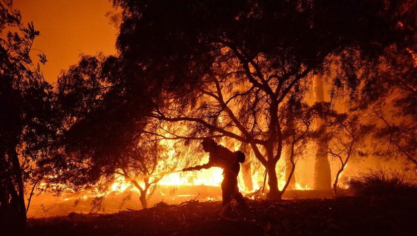 En esta imagen proporcionada por el departamento de bomberos de Santa Barbara, un bombero lucha contra las llamas cerca de un rancho en la zona del cañón de Las Flores, al oeste de Goleta, California, en las primeras horas del jueves 16 de junio de 2016.