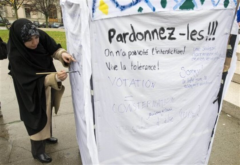 A woman writes slogans on a symbolic minaret erected to protest against the results of a vote in Switzerland at the Place Neuve square in Geneva, Switzerland, Monday, Nov. 30, 2009. Swiss voters overwhelmingly approved a constitutional ban on minarets on Sunday, barring construction of the iconic m