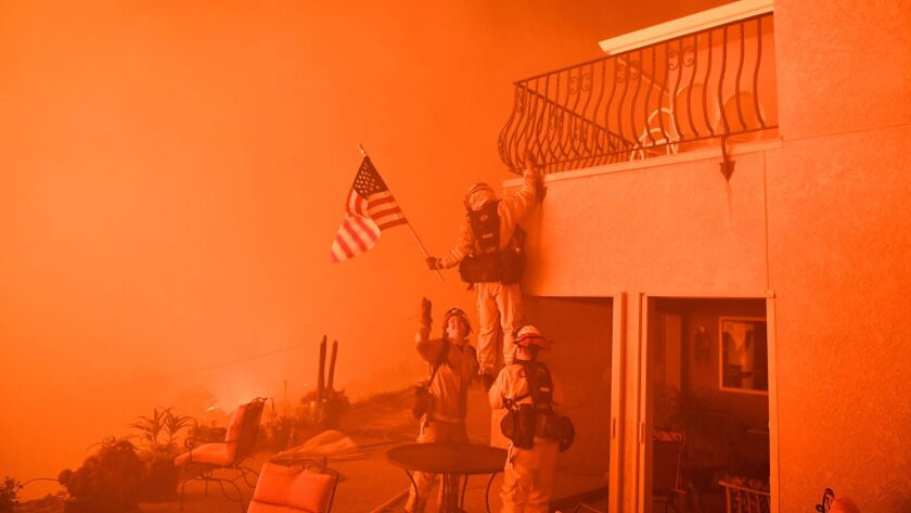 Firefighters save a U.S. flag as flames from the Wall fire close in on a luxury home in Oroville, Calif., on July 8, 2017.