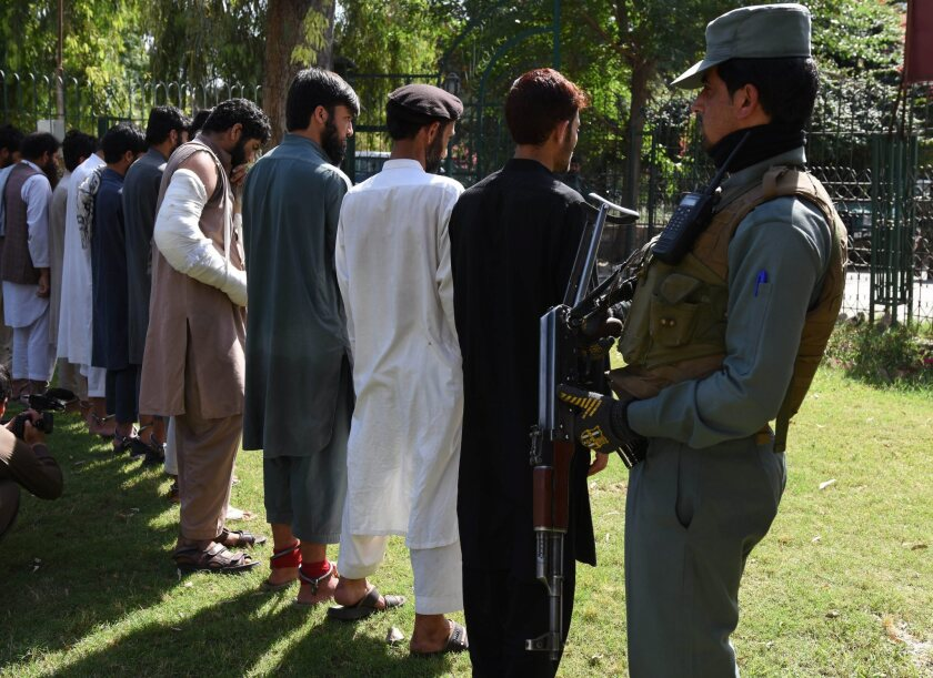 A member of the Afghan security services escorts alleged members of Islamic State arrested during an operation in the Bati Kot district of Nangarhar province, Afghanistan, on May 9.